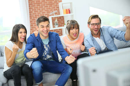 indoor soccer: Cheerful group of friends watching football game on tv
