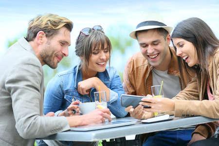 gaseosas: Gente joven en la tienda de café que miran cuadros en Smartphone
