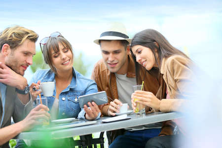 Young people at coffee shop table looking at pictures on smartphone photo