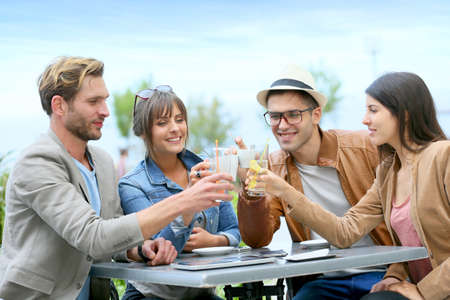 sodas: Group of friends cheering at restaurant terrace