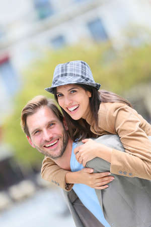 Young man giving piggyback ride to girlfriend in town photo