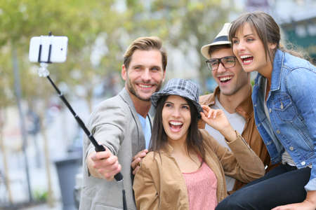 to stick: Group of friends taking picture of themselves with smartphone