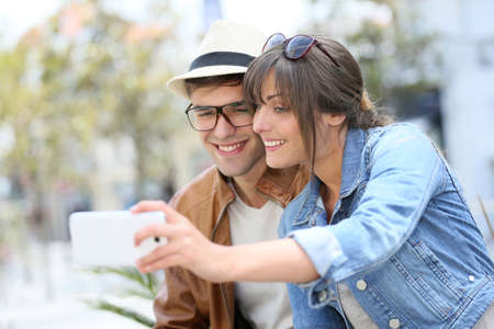 Young trendy couple taking picture with smartphone photo