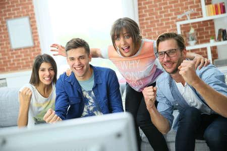 mujer viendo tv: Grupo alegre de amigos viendo el partido de fútbol en la TV