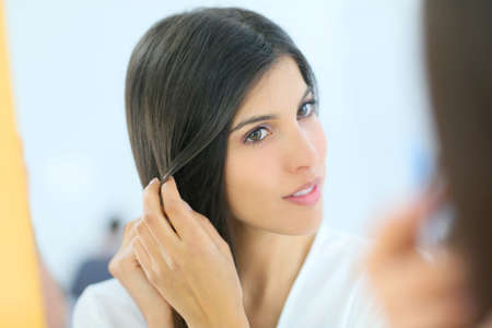 beautycare: Portrait of beautiful young woman looking at her skin