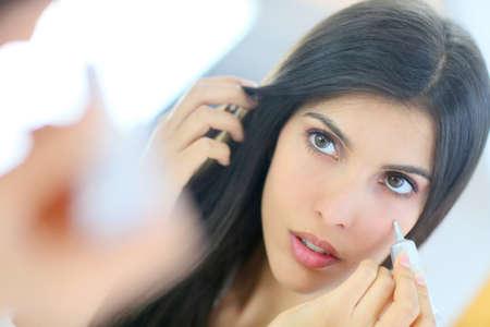 concealer: Bella donna bruna applicando correttore