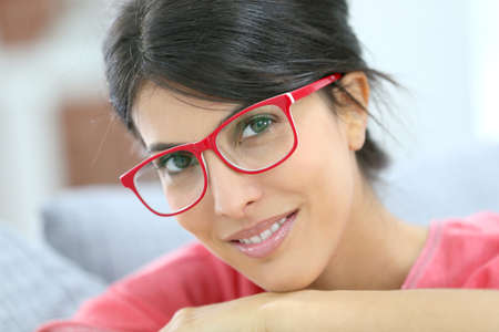 Portrait of beautiful brunette girl wearing red eyeglasses photo