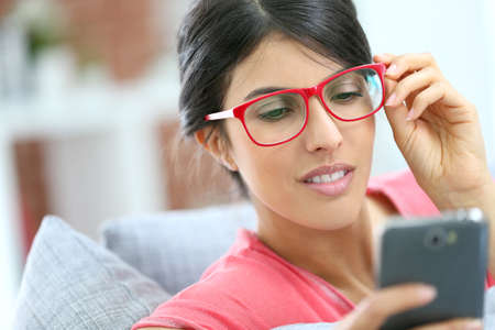Brunette girl with red eyeglasses reading message on smartphone photo