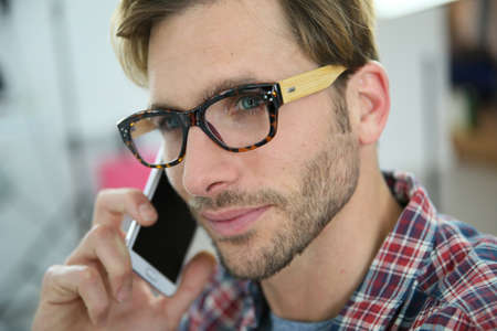 phonecall: Trendy guy with eyeglasses talking on phone in office Stock Photo