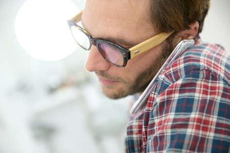 hablando por telefono: Chico de moda con gafas hablando por teléfono en la oficina