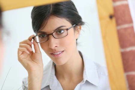 trying on: Portrait of young brunette woman trying eyeglasses on