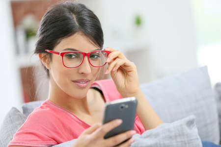 eyeglasses: Brunette girl with red eyeglasses reading message on smartphone
