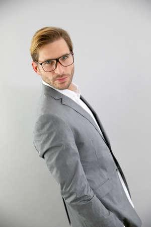 灰色背景: 分離した、灰色の背景の上に立って眼鏡を持ったビジネスマン
