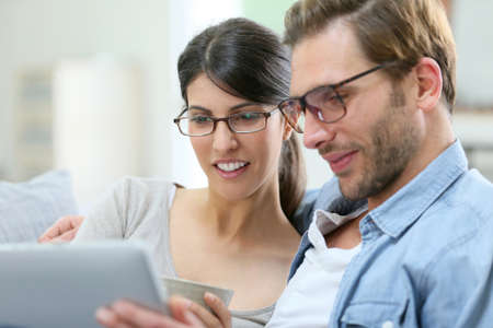 eyeglasses: Couple with eyeglasses websurfing on tablet at home