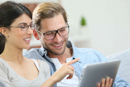websurfing: Couple with eyeglasses websurfing on tablet at home