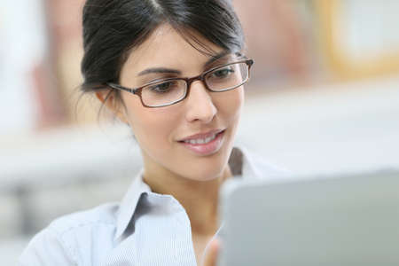 Young woman with eyeglasses using digital tablet photo