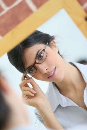 trying: Portrait of young brunette woman trying eyeglasses on