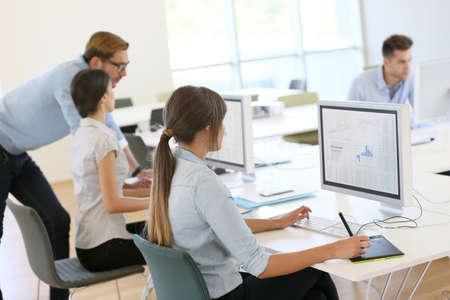 personas trabajando en oficina: Las personas creativas que trabajan en oficina en el ordenador Foto de archivo