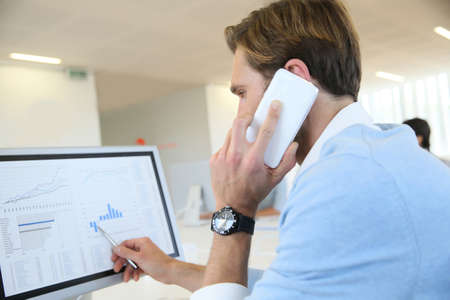 telephone salesman: Bank trader negotiating on the phone from office