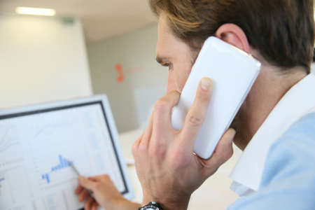 negotiating: Bank trader negotiating on the phone from office