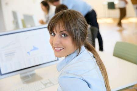 niñas sonriendo: Retrato de alegre oficinista sentado delante de escritorio