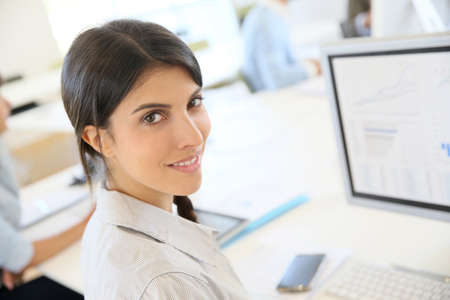 one person: Portrait of young brunette woman working in office Stock Photo