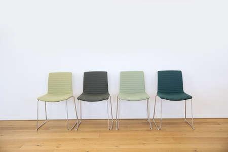 sillon: Fila de 4 sillas verdes fija contra la pared blanca en sala de espera Foto de archivo