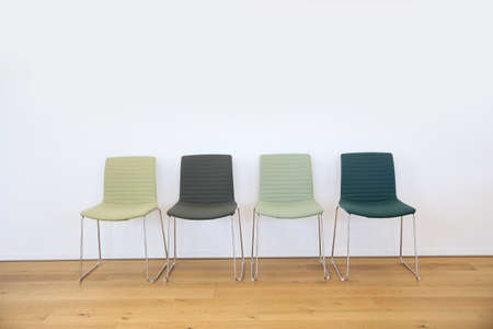 isolated chair: Row of 4 green chairs set against white wall in waiting area Stock Photo