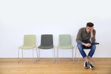fila de personas: Hombre joven en la sala de espera para la entrevista de trabajo