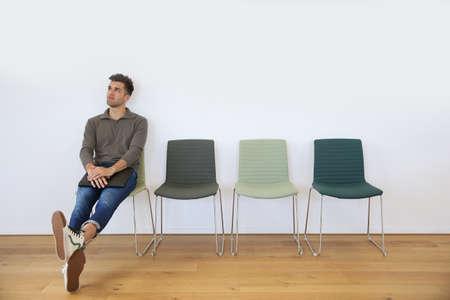 puesto de trabajo: Hombre joven en la sala de espera para la entrevista de trabajo