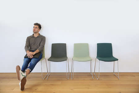 Junger Mann, der im Warteraum für Vorstellungsgespräch