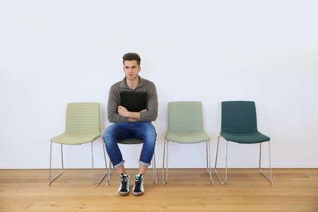 file d attente: Jeune homme dans la salle d'attente pour une entrevue d'emploi