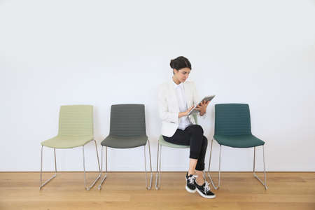 waiting girl: Woman in waiting room using digital tablet, concept