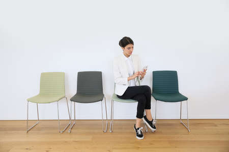 textspace: trendy girl in waiting room sending message with smartphone Stock Photo