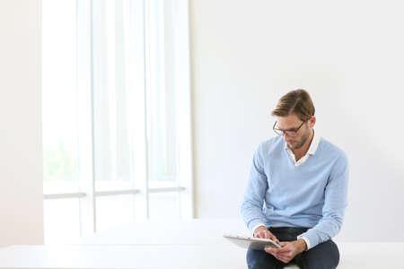 personas trabajando en oficina: Hombre sentado en la mesa, conectado en la tableta digital, fondo blanco