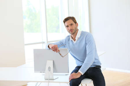 Businessman sitting on table by computer in modern room photo