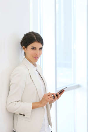 business woman standing: executive woman using smartphone in hallway Stock Photo