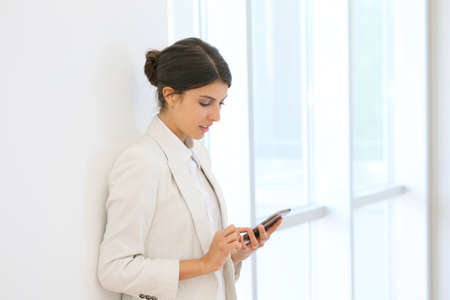 executive woman using smartphone in hallway photo