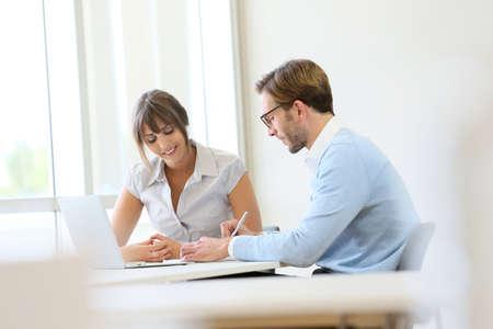 reunion de trabajo: Colegas que trabajan en la oficina moderna con el ordenador portátil