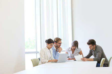 Business people meeting around table in modern space photo