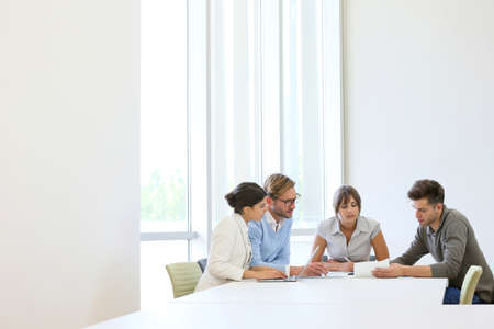 work meeting: Gente de negocios reunidos alrededor de la mesa en el espacio moderno