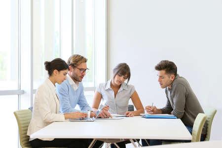 Gente de negocios reunidos alrededor de la mesa en el espacio moderno Foto de archivo - 40819885