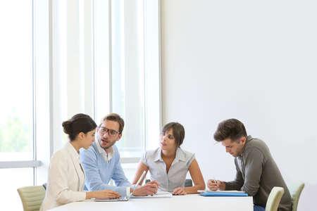 현대적인 공간에서 테이블 주위에 회의 비즈니스 사람들