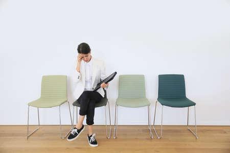 entrevista: Mujer que se sienta en la silla esperando la entrevista de trabajo