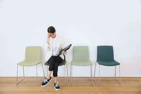 waiting: Woman sitting on chair waiting for job interview