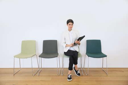 여자는 면접을 기다리는 의자에 앉아서 스톡 콘텐츠