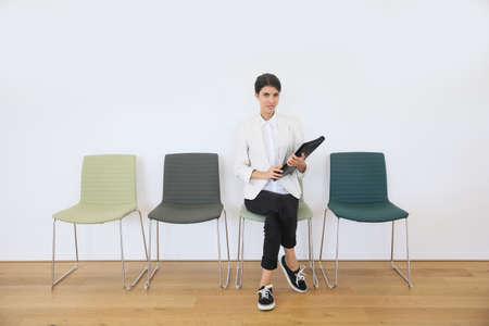 Woman sittin on chair waiting for job interview Stock Photo