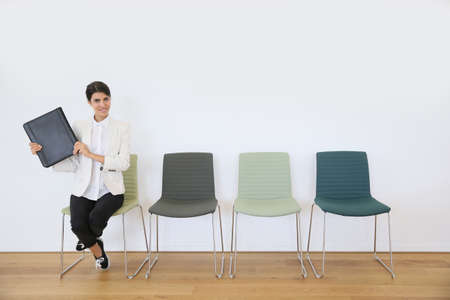 job application: Woman sitting on chair waiting for job interview