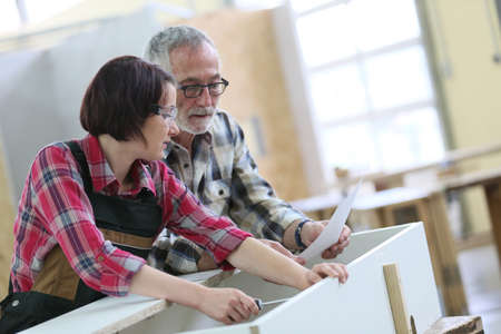 Young woman with senior craftsman in carpentry class Stock Photo