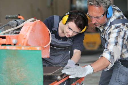 tiler: Tiler showing apprentice how to use thermal grinder Stock Photo